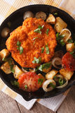 Weiner schnitzel, fried potatoes in a pan closeup. vertical top Royalty Free Stock Photography