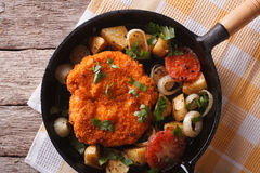 Weiner schnitzel with vegetables in a pan closeup. Horizontal to Stock Photo