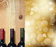 Weinflasche auf einer hölzernen Tabelle und abstrakten Leuchten auf Goldchampagner Stockbilder
