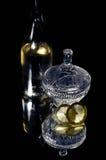 Weinflasche, Kristallvase und 2 Scheiben Zitrone Stockfotografie