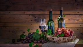 Weinflasche mit Gläsern und Korb von roten Trauben auf Holztisch und Hintergrund stockfotos