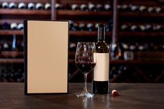 Weinflasche mit Glas und Menü auf dem Tisch Stockfotografie