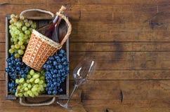Weinflasche, Trauben und Weinglas auf Holztisch lizenzfreies stockfoto