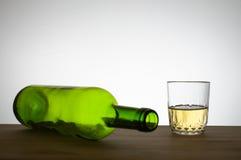 Weinflasche und ein Glas Wein auf einer Tabelle Stockbild