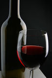 Weinflasche und -glas über schwarzem Hintergrund Lizenzfreies Stockfoto