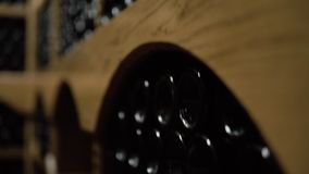 Weinflaschen, die im Stapel am Keller liegen Glasflaschen Rotwein gespeichert im hölzernen Fach im Steinkeller innen stock video