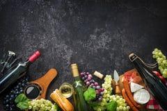 Weinflaschen mit Trauben, Käse, Schinken und Korken lizenzfreie stockfotos