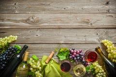 Weinflaschen mit Trauben und Korken auf hölzernem Hintergrund Lizenzfreies Stockfoto