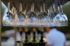 Weingläser gestapelt auf schwarzes Metallhängenden Barglasgestellen in einer Bar lizenzfreie stockfotos