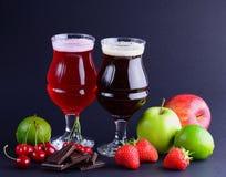 Weingläser Handwerksbier mit einer Zusammenstellung von Früchten und von Beeren über einem schwarzen Hintergrund Getränkehintergr Stockfotos