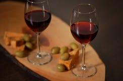 Weingläser mit Rotwein auf Holz mit Käse und grünen Oliven - für gemütlichen Hauptabend Stockfoto