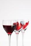 Weingläser mit Rotwein, Herzen und Golfball Stockbild