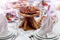 Weingläser, Servietten, Brot und Salat auf dem Tisch Lizenzfreie Stockfotos