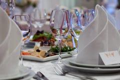 Weingläser, -servietten und -salat auf dem Tisch Stockfotografie