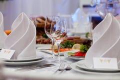 Weingläser, -servietten und -salat auf dem Tisch Stockbilder