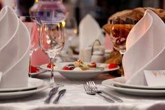 Weingläser, -servietten und -salat auf dem Tisch Stockbild
