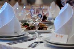 Weingläser, -servietten und -salat auf dem Tisch für das Bankett Lizenzfreies Stockbild