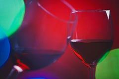 Weingläser und bunte Lichter Stockfotos