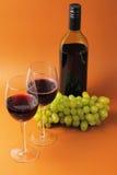 Weingläser und -flasche mit Trauben Stockfoto