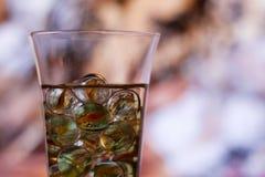 Weinglas mit Marmoren gegen abstrakten Hintergrund Stockfotos