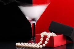 Weinglas mit Nebel und Perl bördelt in geöffnetem Papier-giftbox auf schwarzem und rotem Hintergrund Stockbild