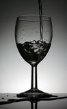 Weinglas mit strömenden Wasser, das auf einer schwarzen Tabelle steht Lizenzfreie Stockfotografie