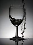 Weinglas mit strömenden Wasser, das auf einer schwarzen Tabelle steht lizenzfreie stockfotos
