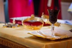 Weinglas und -brot der heiligen Kommunion während der Heirat der traditionellen Zeremonie in der Kirche Lizenzfreies Stockbild