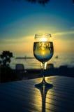 Weinglas und gelber Sonnenuntergang in der Küste Stockfoto