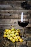 Weinglas und neues Bündel weiße Trauben auf antikem hölzernem BAC lizenzfreie stockfotografie