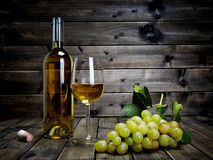 Weinglas und neues Bündel weiße Trauben auf antikem hölzernem BAC lizenzfreies stockbild