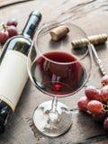Weinglas, Weinflasche und Trauben auf hölzernem Hintergrund Wein ta Stockfotografie