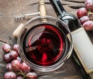 Weinglas, Weinflasche und Trauben auf hölzernem Hintergrund Wein ta Lizenzfreies Stockbild