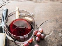 Weinglas, Weinflasche und Trauben auf hölzernem Hintergrund Wein ta Stockbild