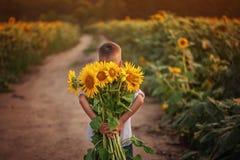 Weinig aanbiddelijk de holdingsboeket van de jong geitjejongen van zonnebloemen in de zomerdag Kind die bloemen geven royalty-vrije stock afbeeldingen