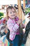 Weinig aanbiddelijk glimlachend meisje die een paard berijden op rotondecarrousel bij funfair stock foto's