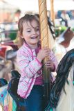 Weinig aanbiddelijk glimlachend meisje die een paard berijden op rotondecarrousel bij funfair stock afbeelding