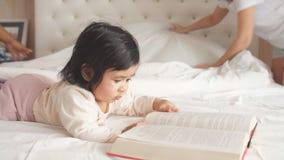 Weinig aanbiddelijk meisje concentreerde zich bij het lezen van een boek, weinig boekenwurm stock video