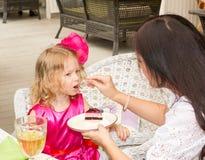 Weinig aanbiddelijk meisje die 3 jaar vieren verjaardags en eet cake Stock Afbeelding