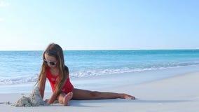 Weinig aanbiddelijk meisje die zandkasteel maken en bij tropisch strand spelen stock video