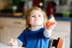 Weinig aanbiddelijk peutermeisje die grote rode appel eten Vitamine en gezond voedsel voor kleine kinderen Portret van mooi stock foto's