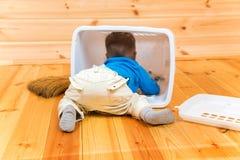 Weinig actieve jongen helpt om het huis schoon te maken die binnenbak krijgen Royalty-vrije Stock Foto's
