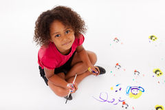 Weinig Afrikaans Aziatisch meisje die op de vloer schilderen royalty-vrije stock fotografie