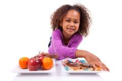 Weinig Afrikaans Aziatisch meisje die tussen vruchten of suikergoed aarzelen Royalty-vrije Stock Foto