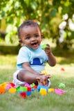 Weinig Afrikaanse Amerikaanse babyjongen die in het gras spelen Stock Afbeelding