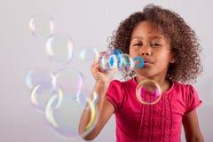 Weinig Afrikaanse Aziatische meisjes blazende zeepbels Stock Afbeeldingen