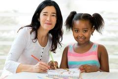 Weinig Afrikaanse meisje en leraar die zich samentrekken royalty-vrije stock afbeelding