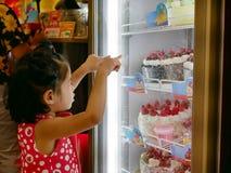 Weinig Aziatisch babymeisje die en wat betreft de bakkerijkoelkast kijken aangezien zij voor mooie cakes hongerig was royalty-vrije stock foto