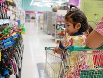 Weinig Aziatisch babymeisje in een boodschappenwagentje, wordt opgewekt om vele fietsen in verschillende kleuren in een supermark stock foto