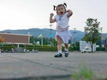 Weinig Aziatisch babymeisje geniet openlucht van lopen stock foto